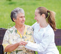 Elderly care women with her caretaker in the nature Stock Photography