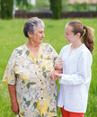 Elderly care women with her caretaker walking in the nature Royalty Free Stock Image