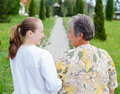 Elderly care women with her caretaker walking in the nature Stock Photo