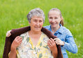 Elderly care young girl wrap her mother with a warm sweater Royalty Free Stock Images