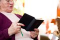 Elderly caucasian woman with hands holding bible as she reads Royalty Free Stock Image