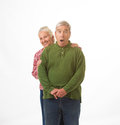 Elderly couple in christmas colors an isolated on a white background with happy and surprised expressions Stock Photos
