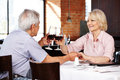 Elderly couple clink glasses with red wine in a restaurant Royalty Free Stock Photos