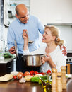 Elderly couple cooking healthy food at home kitchen Stock Images