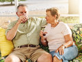 Elderly couple drinking on patio photo of a out of wine glasses together Royalty Free Stock Photography