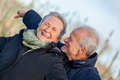 Elderly couple embracing and celebrating the sun attractive in warm clothing standing clue together with outstretched arms closed Stock Images