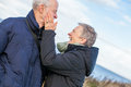 Elderly couple embracing and celebrating the sun attractive in warm clothing standing clue together with outstretched arms closed Stock Photography