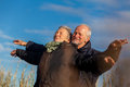 Elderly couple embracing and celebrating the sun attractive in warm clothing standing clue together with outstretched arms closed Royalty Free Stock Photos