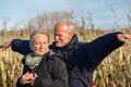 Elderly couple embracing and celebrating the sun attractive in warm clothing standing clue together with outstretched arms closed Royalty Free Stock Photo