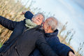 Elderly couple embracing and celebrating the sun attractive in warm clothing standing clue together with outstretched arms closed Stock Photo
