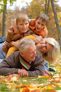 Elderly couple and grandchildren lie happy beautiful in the autumn park Royalty Free Stock Images