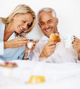 Elderly couple having breakfast on the bed Royalty Free Stock Photos