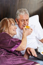 Elderly couple having breakfast in hotel bed happy together a Stock Image