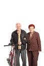 Elderly couple holding hands and pushing a bike isolated on white background Stock Photo