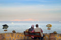 Elderly couple hugging and looking at the sea sitting on a bench Stock Image
