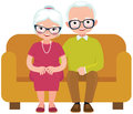 Elderly couple husband and wife sitting on couch embracing