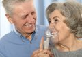 Elderly couple with inhaler cute smiling making inhalation Stock Photography