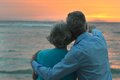 Elderly couple in love at sunset on a summer evening watching sea Stock Images