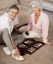 Elderly couple playing backgammon while on floor Royalty Free Stock Images