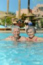 Elderly couple in pool swimming at hotel resort Stock Photography