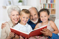 Elderly couple reading to their grandchildren as they all sit close together on a sofa Royalty Free Stock Images