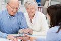 Elderly couple receiving financial advice smiling from a female broker who is showing them a calculator Stock Images