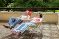 The elderly couple relax in lounges on sunny terrace summer day Stock Photos