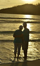 Elderly couple rest at tropical beach at sunset Royalty Free Stock Photo