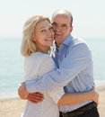 Elderly couple at sea shore happy smiling hugging in warm season Stock Photography