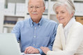 Elderly couple sharing a laptop computer as they read information on the screen while sitting in an office Royalty Free Stock Photography