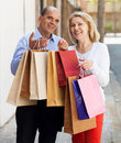 Elderly couple with shopping bags in hands and smiling together outdoor Stock Photos