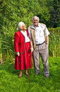 Elderly couple standing hand in hand in their garden happy Royalty Free Stock Photos