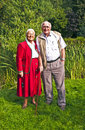 Elderly couple standing hand in hand in their garden happy Royalty Free Stock Photo