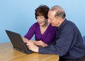 Elderly couple together using a laptop Stock Image