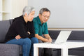 Elderly couple using laptop computer at home Stock Photo