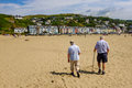 Elderly couple walking on beach rear view of an across a towards a seaside town a sunny day aberdovey gwynedd wales uk Stock Photography