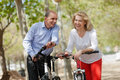 Elderly couple walking in summer park happy with bicycles Royalty Free Stock Images