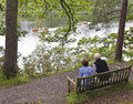 An Elderly Couple Watch Rowboats in a Lake Royalty Free Stock Photo