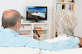 Elderly couple watching television sitting comfortably on a sofa with their backs to the camera holding the remote control Royalty Free Stock Images