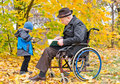 Elderly disabled man with his grandson men sitting reading book wheelchair enjoying day out autumn park little who is standing Royalty Free Stock Photos