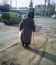 Elderly disabled woman with a stick walking down the street