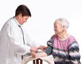 Elderly doctor and patient . Measuring pressure. Royalty Free Stock Image