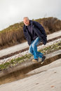 Elderly energetic man running along a beach at the edge of bay on cold day as he exercises to remain fit and healthy while Stock Images