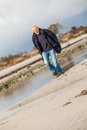 Elderly energetic man running along a beach at the edge of bay on cold day as he exercises to remain fit and healthy while Royalty Free Stock Photography