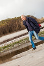 Elderly energetic man running along a beach at the edge of bay on cold day as he exercises to remain fit and healthy while Royalty Free Stock Images