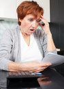 Elderly female sorting through her old receipts woman at home sad businesswoman with document Royalty Free Stock Images