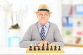 Elderly gentleman posing behind a chessboard indoors Royalty Free Stock Photos