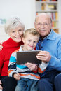Elderly grandparents with their little grandson cute sitting on laps grouped together on a couch in the living room reading Royalty Free Stock Photography