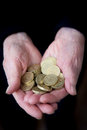 Elderly hands holding british pound coins concept photograph highlighting the high cost of living for pensioners Royalty Free Stock Photos
