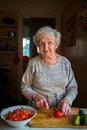 An elderly happy woman chops vegetables for a salad in the kitchen. Royalty Free Stock Photo